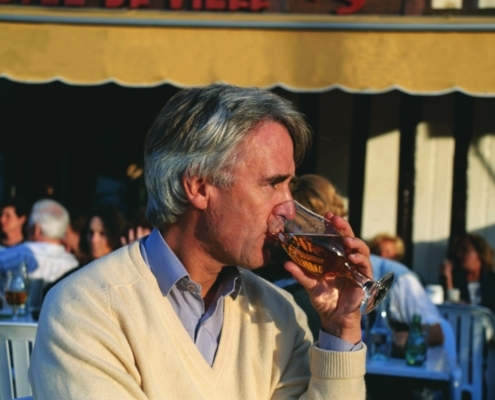Man enjoying a beer in the early evening at a harbour side cafe in Honfleur, Normandy, France
