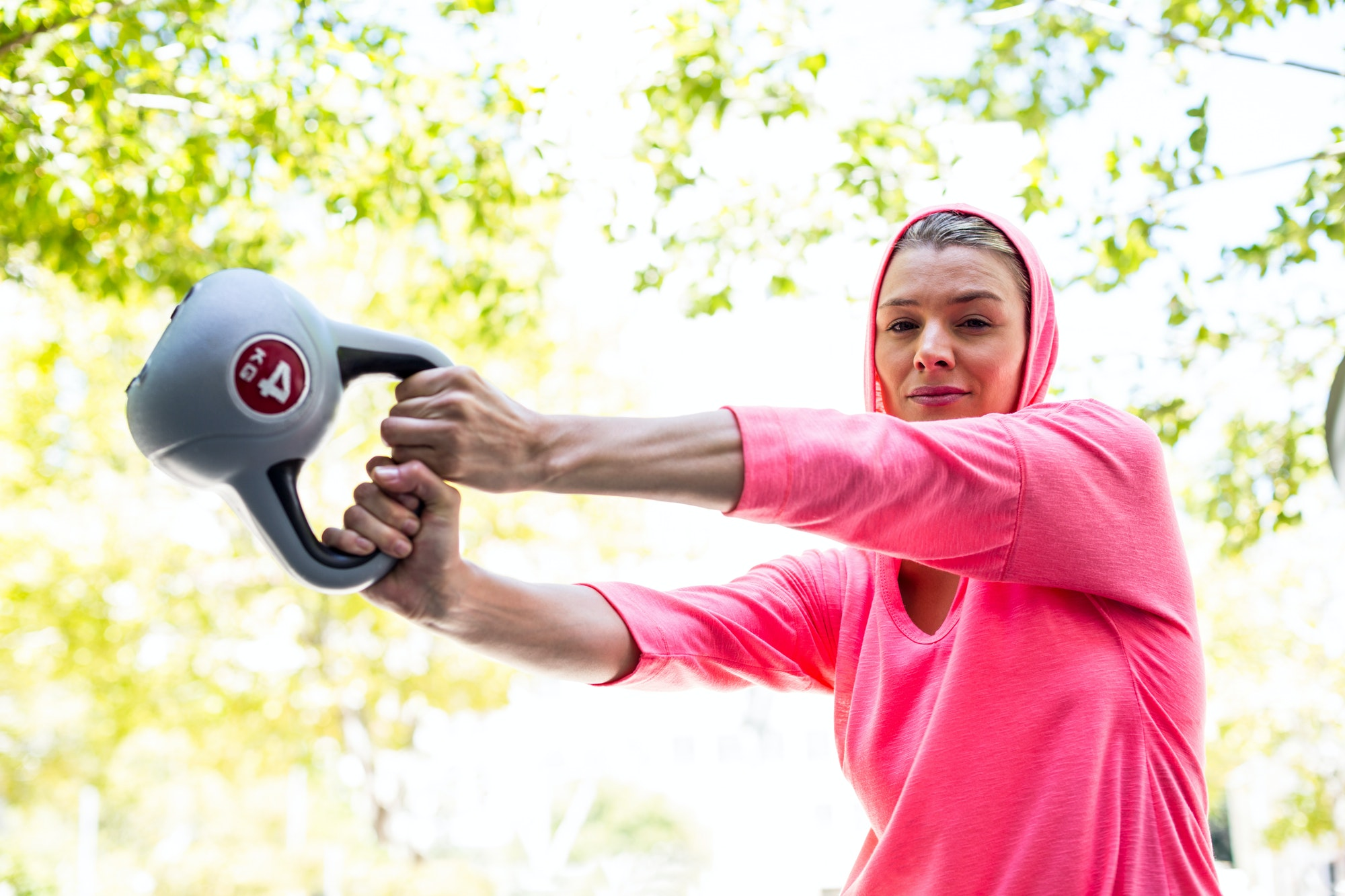 A pretty woman in a pink outfit doing exercise with a weight on a sunny day
