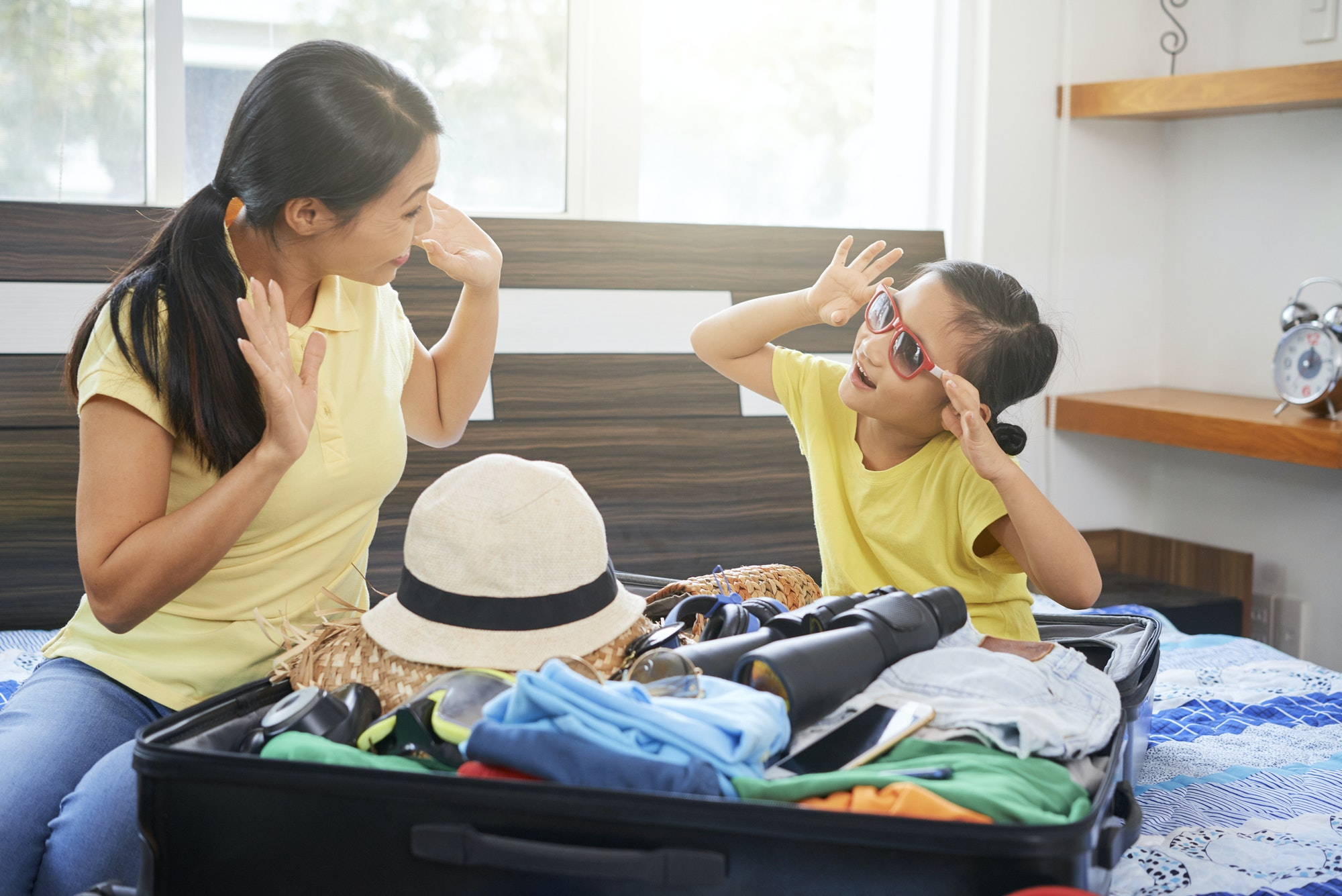 Family packing clothes in suitcase