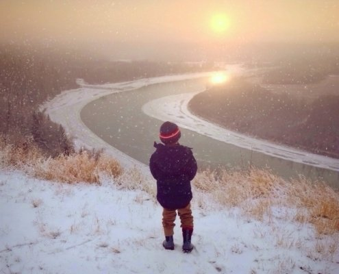 Young child watches the sun go down in winter